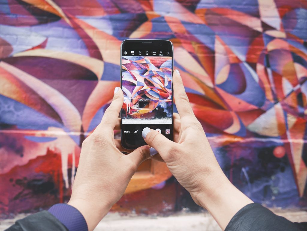 Person takes photo of some bright street art on their phone